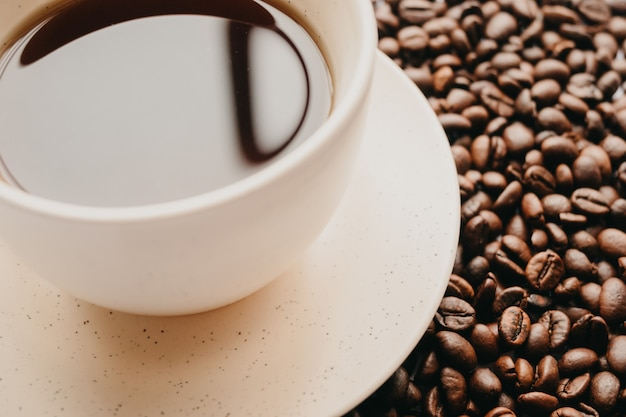 Closeup shot of a cup of coffee with coffee beans on white
