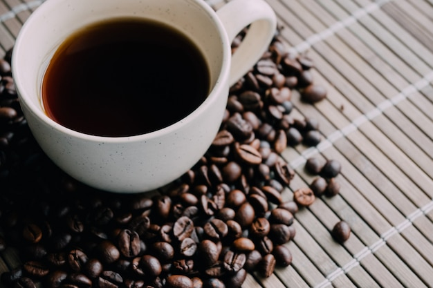Closeup shot of a cup of coffee with coffee beans