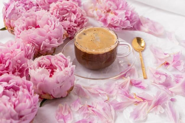 Colpo del primo piano di una tazza di caffè istantaneo su un piattino sul tavolo con peonie rosa su di esso