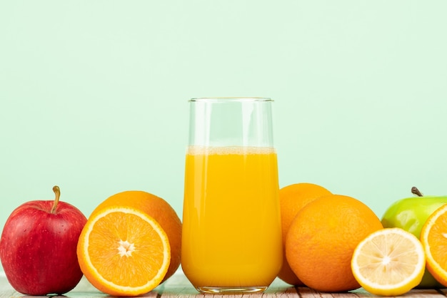 Closeup shot of a cup of invigorating juice surrounded by fruits on a wooden table