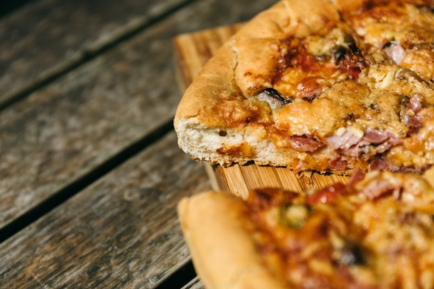 Closeup shot of a cut pizza on a wooden desk