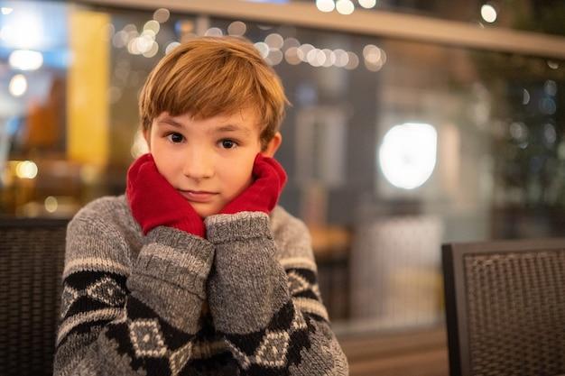 Colpo del primo piano di un ragazzo biondo carino seduto con le mani in guanti rossi sulle guance