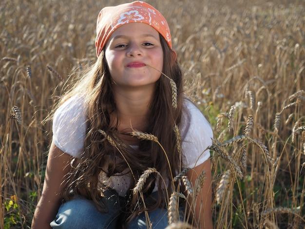 Colpo del primo piano di una bambina sveglia in una bandana che si siede nel campo di grano