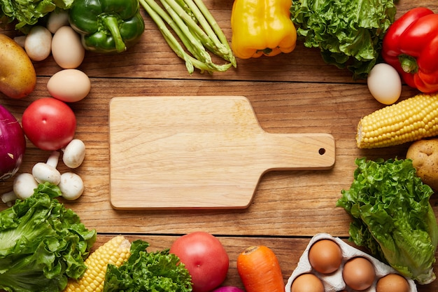 Closeup shot of cutting board and fresh vegetables on wooden