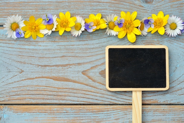 Closeup shot of daisy flowers and a chalkboard with space for text on a wooden surface