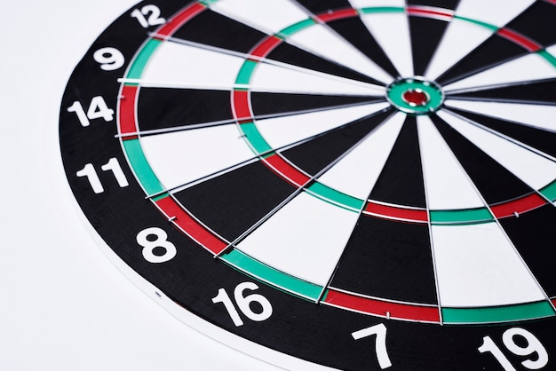 Closeup shot of dartboard lying on the white surface