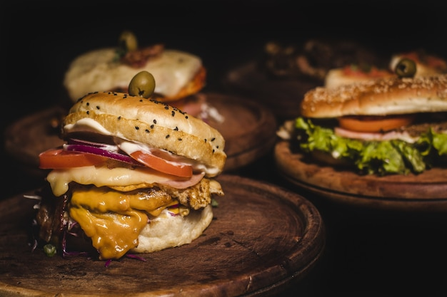 Closeup shot of delicious burgers on a wooden tray