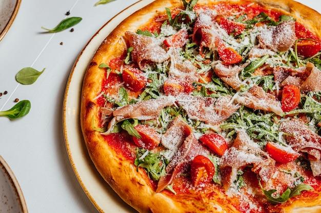 Primo piano di una deliziosa pizza al formaggio con prosciutto, pomodori e verdure su un piatto