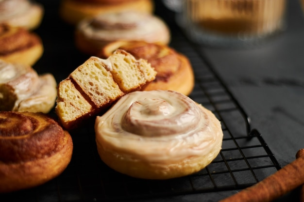 Closeup shot of delicious cinnamon rolls with white glaze on a black table