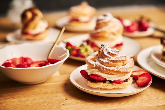 Closeup shot of delicious cream puff with strawberries on a wooden table