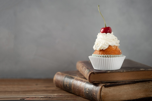 Closeup shot of a delicious cupcake with cream and cherry on top on books