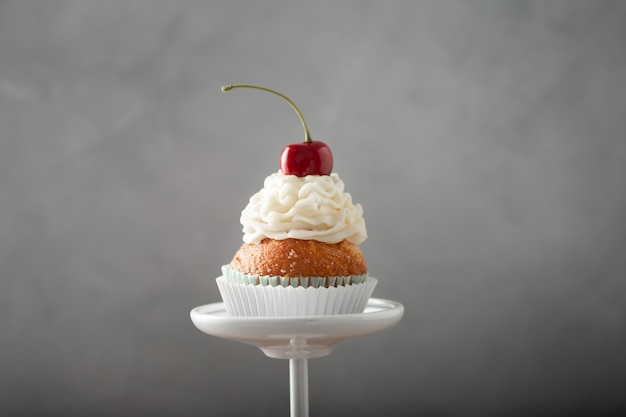 Closeup shot of a delicious cupcake with cream and cherry on top on a dessert stand