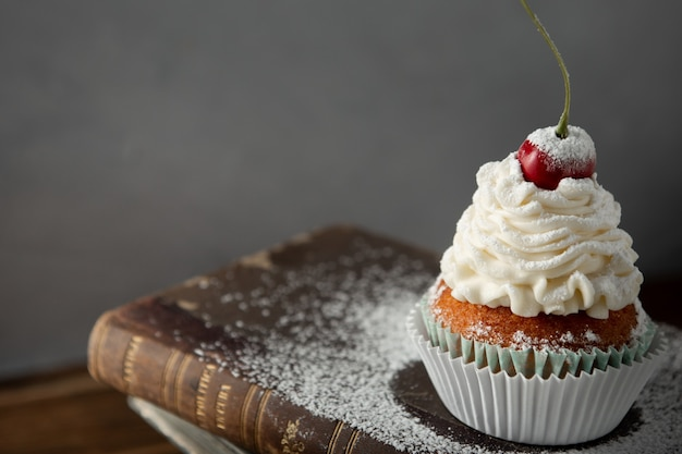 Closeup shot of a delicious cupcake with cream, powdered sugar, and a cherry on top on book