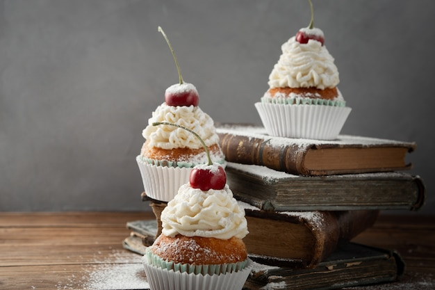 Closeup shot of delicious cupcakes with cream, powdered sugar, and a cherry on top on books