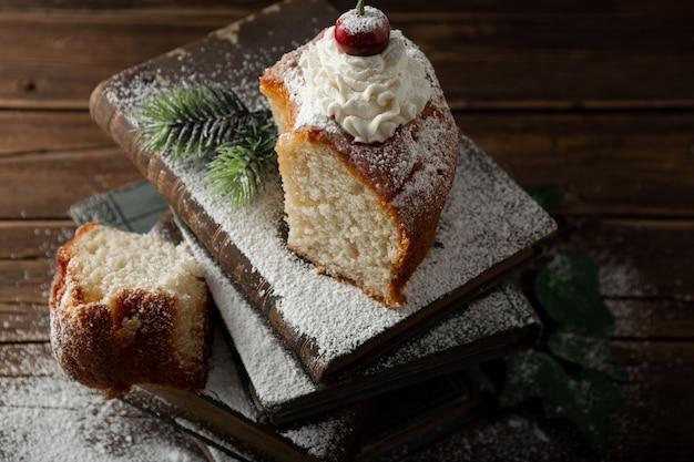 Closeup colpo di delizioso dessert con panna, zucchero a velo e una ciliegina sulla torta sui libri