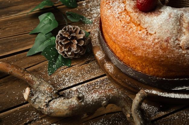 Colpo del primo piano di un delizioso pan di spagna con fragole, una pigna e mirtilli rossi sul tavolo