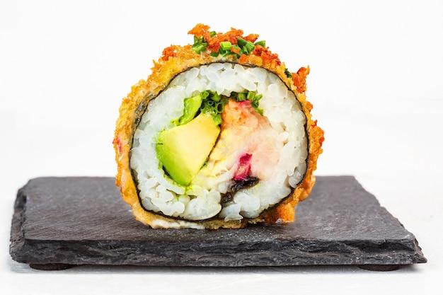 Primo piano di un delizioso rotolo di sushi con condimenti su sfondo bianco