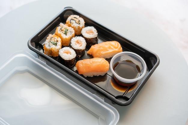 Primo piano di deliziosi rotoli di sushi in una scatola di plastica su una superficie bianca