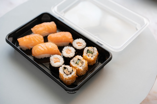 Closeup shot of delicious sushi rolls in a plastic box on a white surface