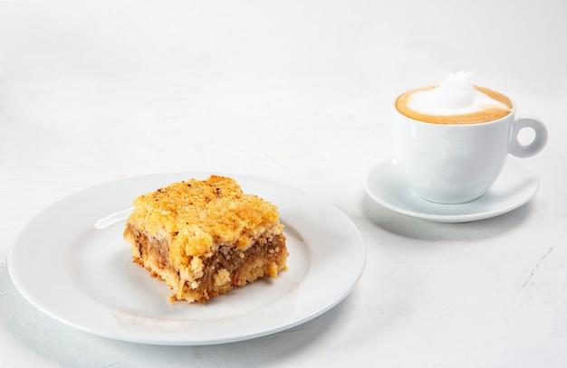 Colpo del primo piano di un piatto da dessert vicino a una tazza di cappuccino isolato su priorità bassa bianca
