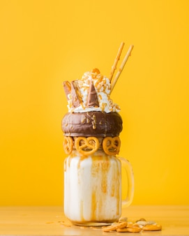 Closeup shot of a dessert with chocolate doughnut, whipped cream and salty pastry on a drinking jar