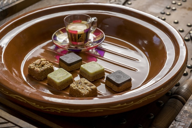 Closeup shot of different types of square-shaped sweets with tea on a wooden tray