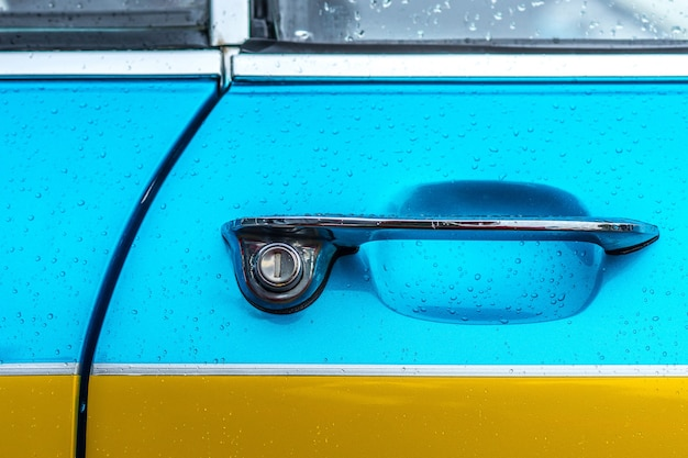 Closeup shot of the door handle of a blue and yellow car