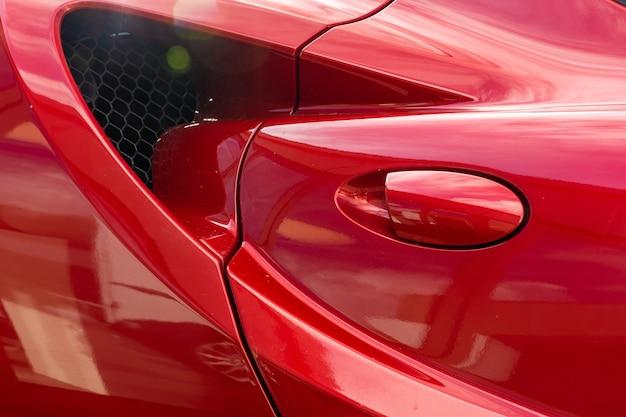 Colpo del primo piano della maniglia della porta di una moderna automobile rossa