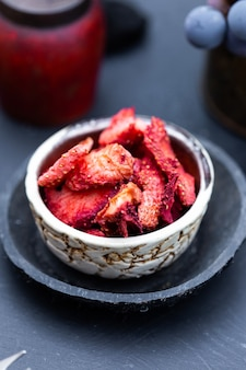 Closeup shot of dried strawberries in a rustic iron bowl