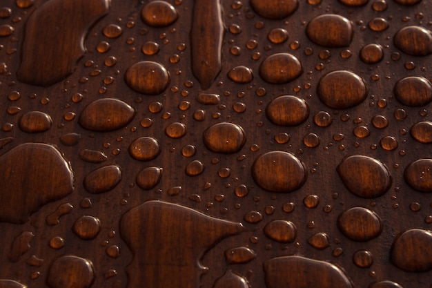 Closeup shot of drips of water on a wooden surface