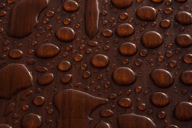 Colpo del primo piano di gocce d'acqua su una superficie in legno