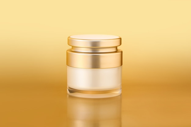 Closeup shot of an elegant gold skincare container on a gold background