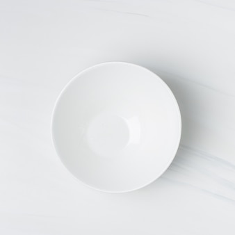 Closeup shot of an empty white ceramic bowl on a white wall
