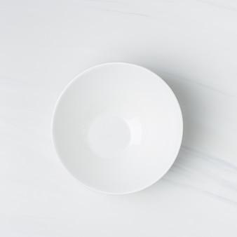 Colpo del primo piano di una ciotola di ceramica bianca vuota su una parete bianca