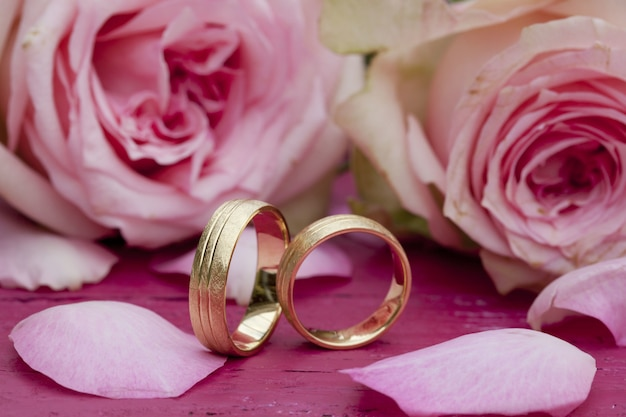Closeup shot of engagement rings with beautiful pink roses on the table