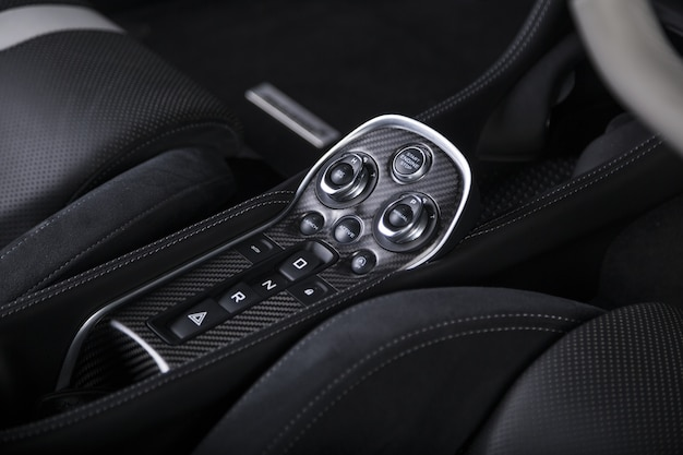 Colpo del primo piano dei pulsanti di avviamento del motore all'interno di un'auto sportiva moderna Foto Gratuite