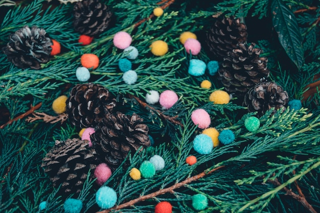 Primo piano di rami di alberi sempreverdi e pigne con piccoli pompon colorati