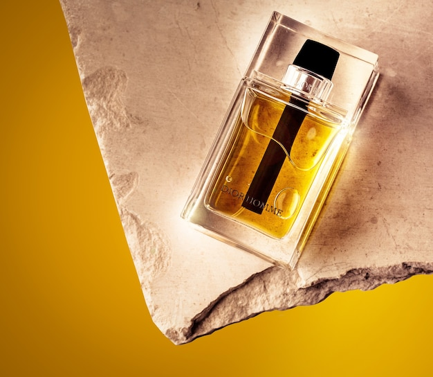 Colpo del primo piano di una famosa bottiglia di profumo con uno sfondo giallo
