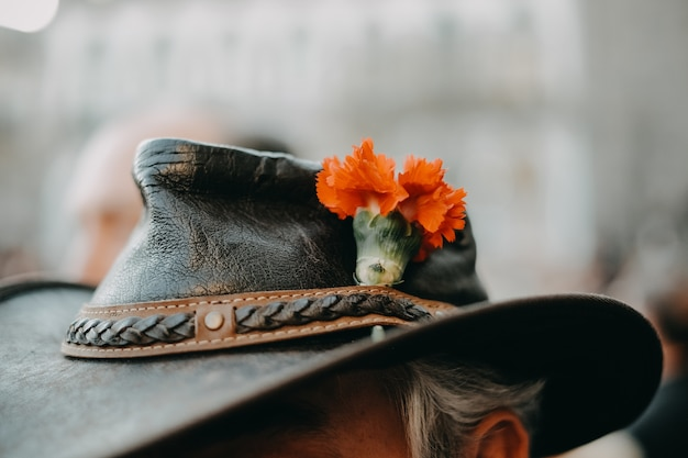 Closeup shot of a fancy cowboy hat with an orange flower on it worn by an elderly person