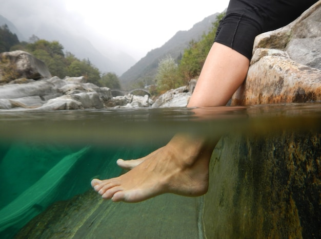 Closeup shot of feet underwater in a river with mountains in ticino, switzerland.