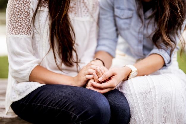 Colpo del primo piano delle coppie femminili che tengono le mani con uno sfondo sfocato