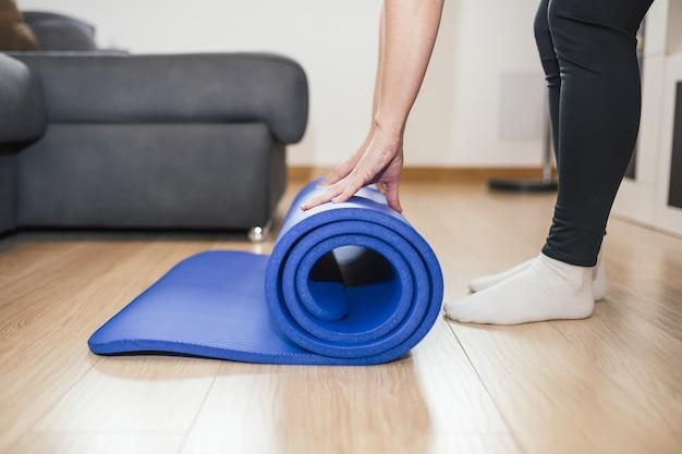 Primo piano di una donna che piega un tappetino da yoga blu dopo essersi allenata a casa