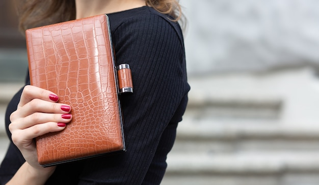 Closeup shot of a female hand holding small leather brown  clutch. space for text