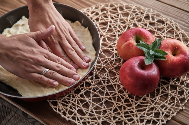 Colpo del primo piano delle mani femminili che preparano la torta di mele rossa