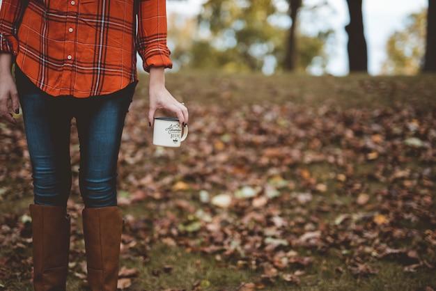 Colpo del primo piano di una femmina che tiene una tazza con uno sfondo sfocato