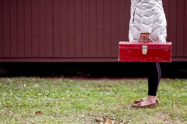 Colpo del primo piano di una donna che tiene una cassetta degli attrezzi