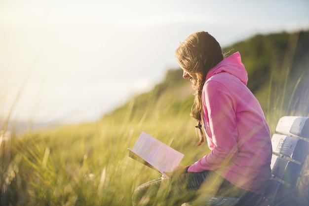 Il colpo del primo piano di una femmina che si siede sul banco mentre legge la bibbia in un campo di erba