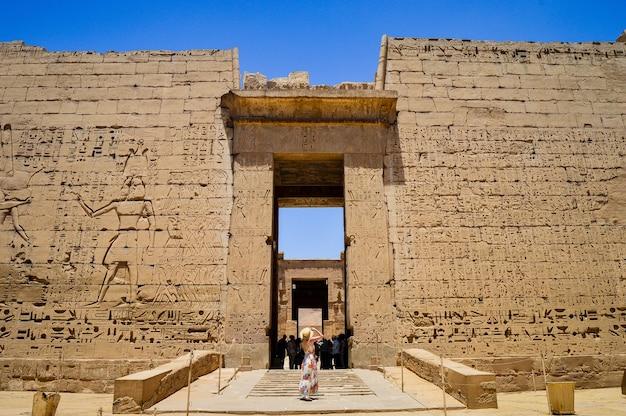 Primo piano di una donna in piedi di fronte a un tempio di medinet habu in egitto