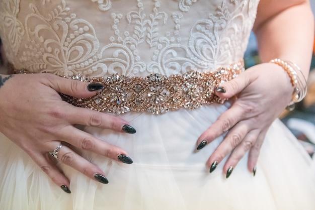 Colpo del primo piano di una donna che prova su un bellissimo abito da sposa fatto a mano