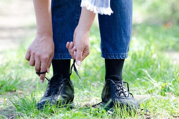 Colpo del primo piano di una femmina che lega i suoi lacci delle scarpe su un sentiero con erba
